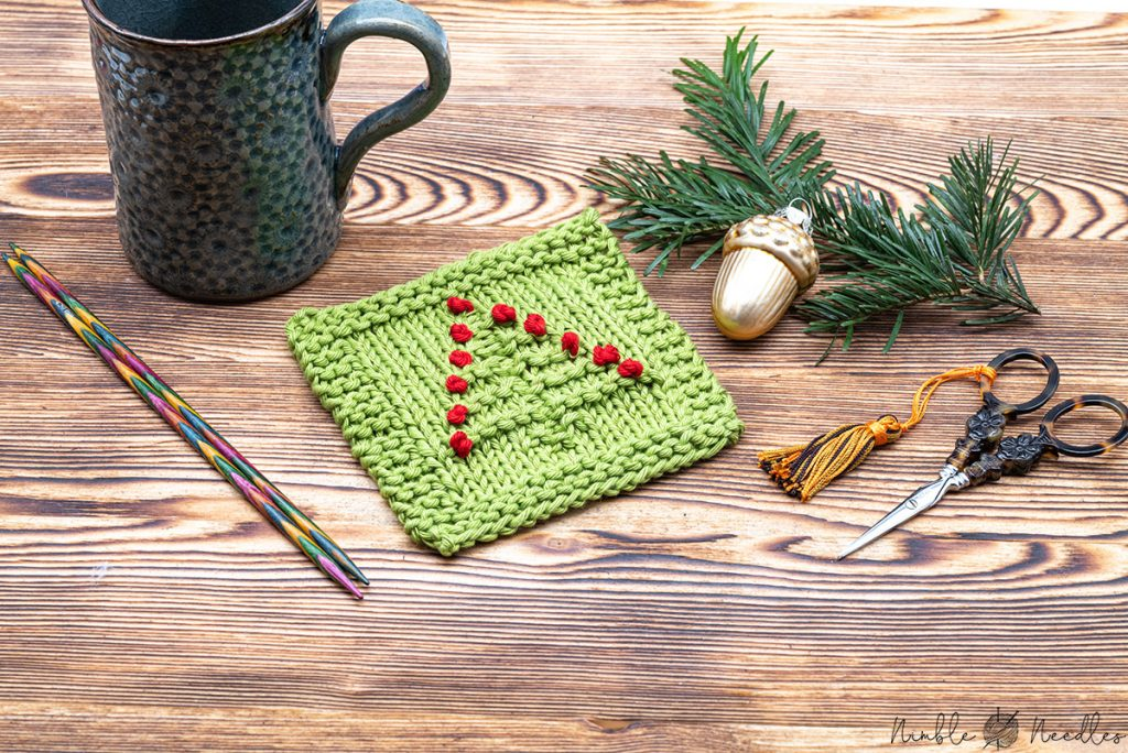 a knitted christmas coaster embelished with embroidery