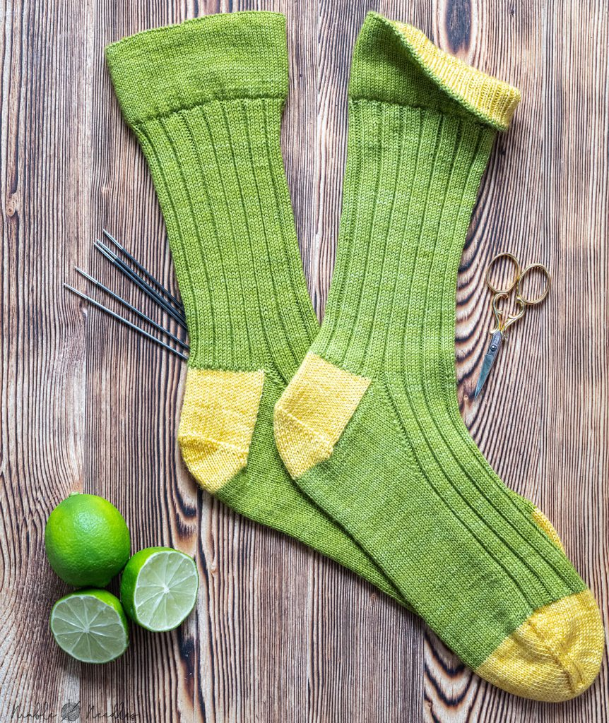 ribbing socks in two colors with inverted hem on a wooden board