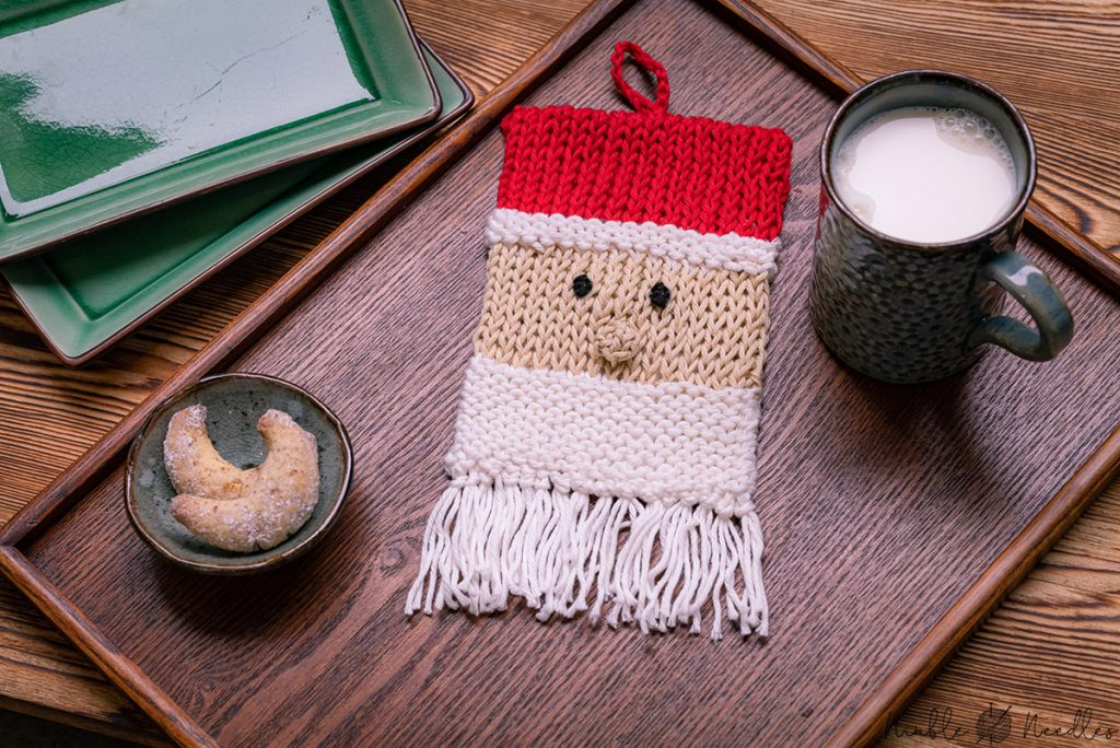 santa claus potholder knitting pattern decorated on a wooden tray