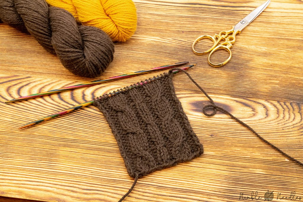 a cable stitch swatch knit with yak yarn and two skeins in the background