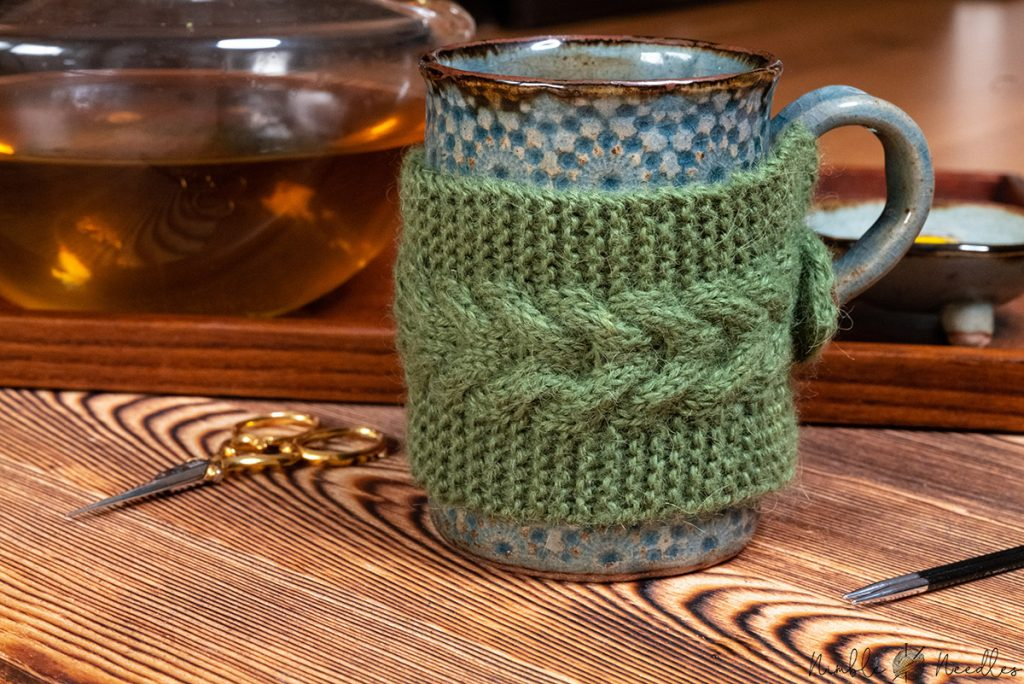 a knitted mug cozy with cable stitch details - close-up