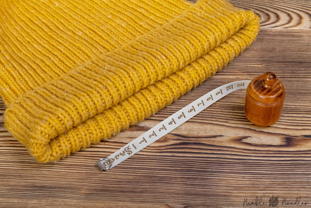 a retractable measuring tape for knitters with a hat in the background