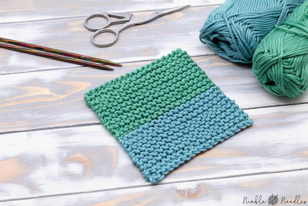 a two colored knitted coaster in teal and green