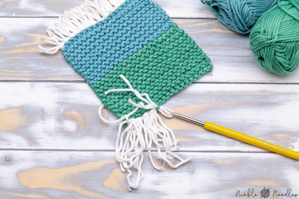 attaching fringes to a knitted coaster using a crochet hook
