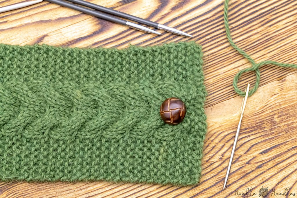 attaching the button to the mug cozy with a tapestry needle