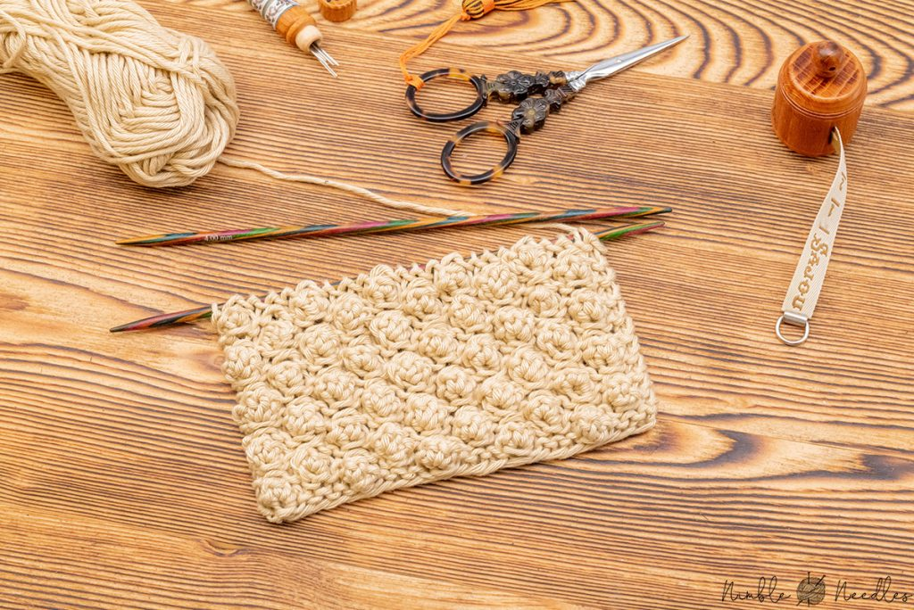 A swatch with the garter stitch bobble stitch knitting pattern and various tools in the background