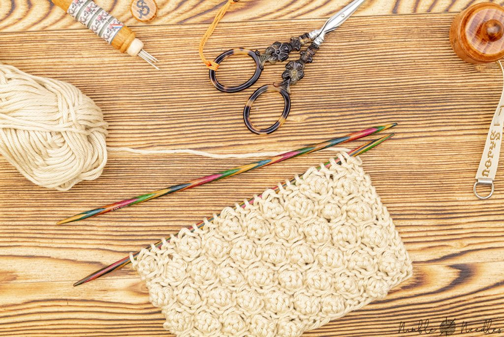 swatch with garter stitch bobbles and knitting needles