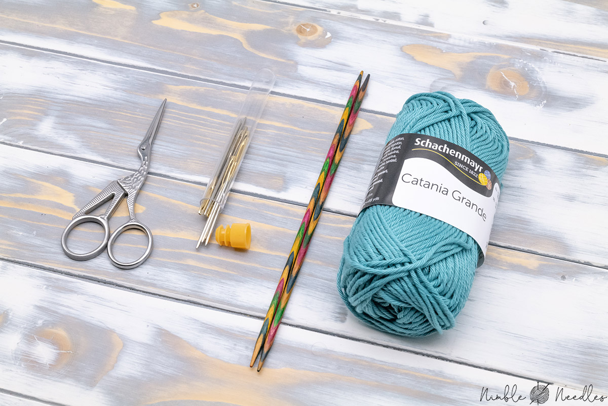 materials you need for this knitted coaster: needles, yarn, scissors, and a tapestry needle