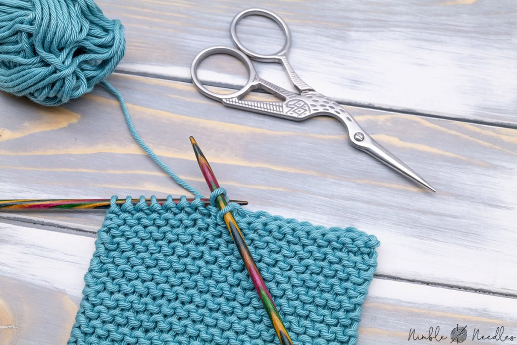 a swatch with a half-finished bind-off and some knitting tools in the background