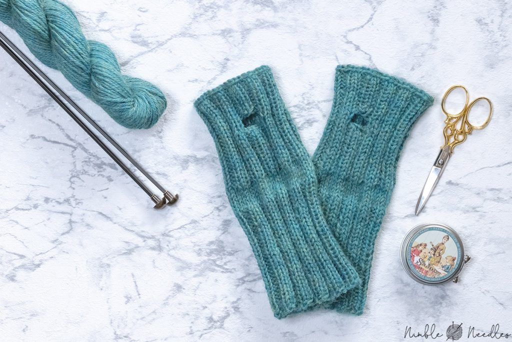the finished fingerless gloves after closing the seam next to each other on a flat marble tray