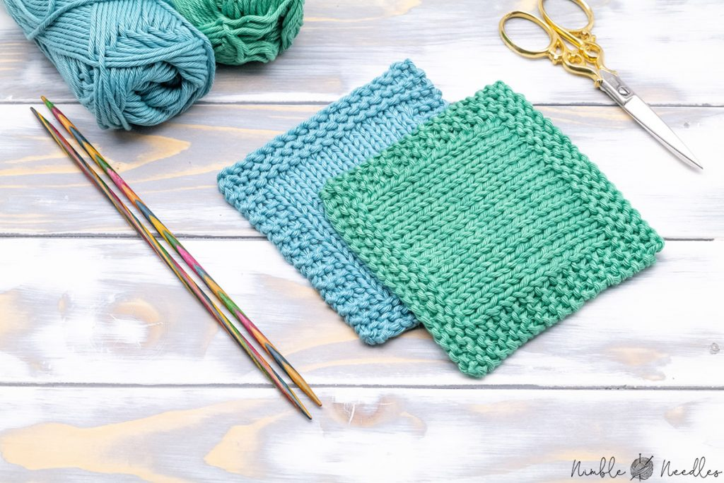 two simple square knitted coasters in teal and green on a wooden board with the knitting needles next to them