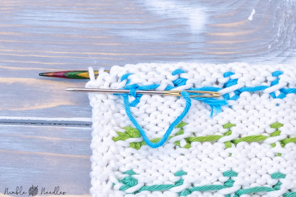 tying a knot to weave in the bobble stitch with two colors on the backside
