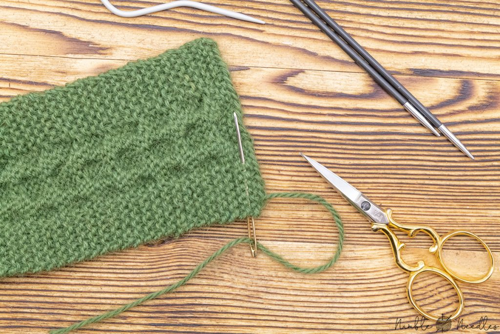 weaving in the tails with a tapestry needle to finish the cozy