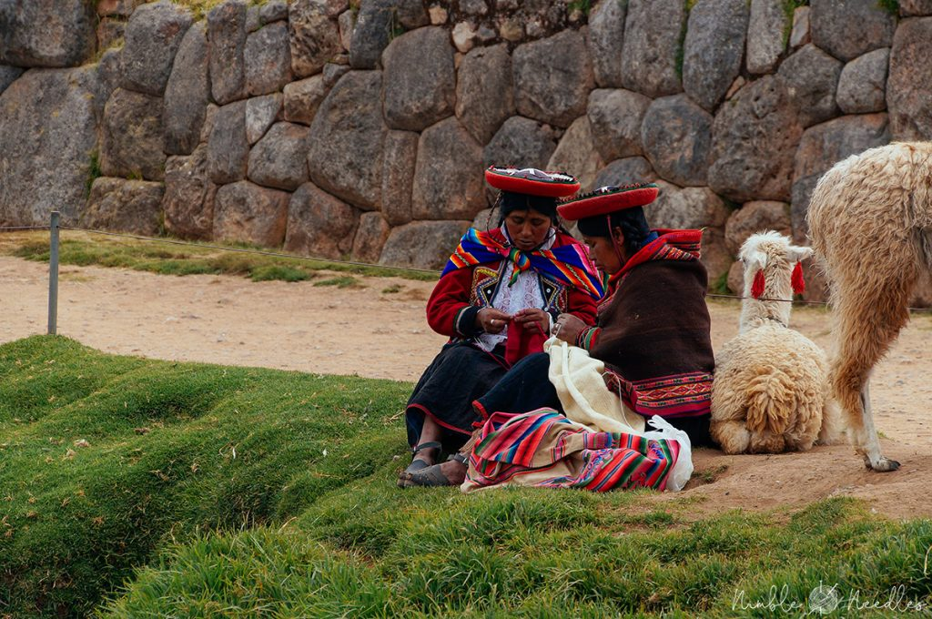 a group of peruvian women knitting with alpaca yarn and two alpaca in the background