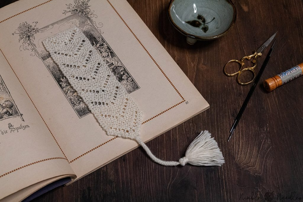 the knitted bookmark inside an old book with knitting tools on the side