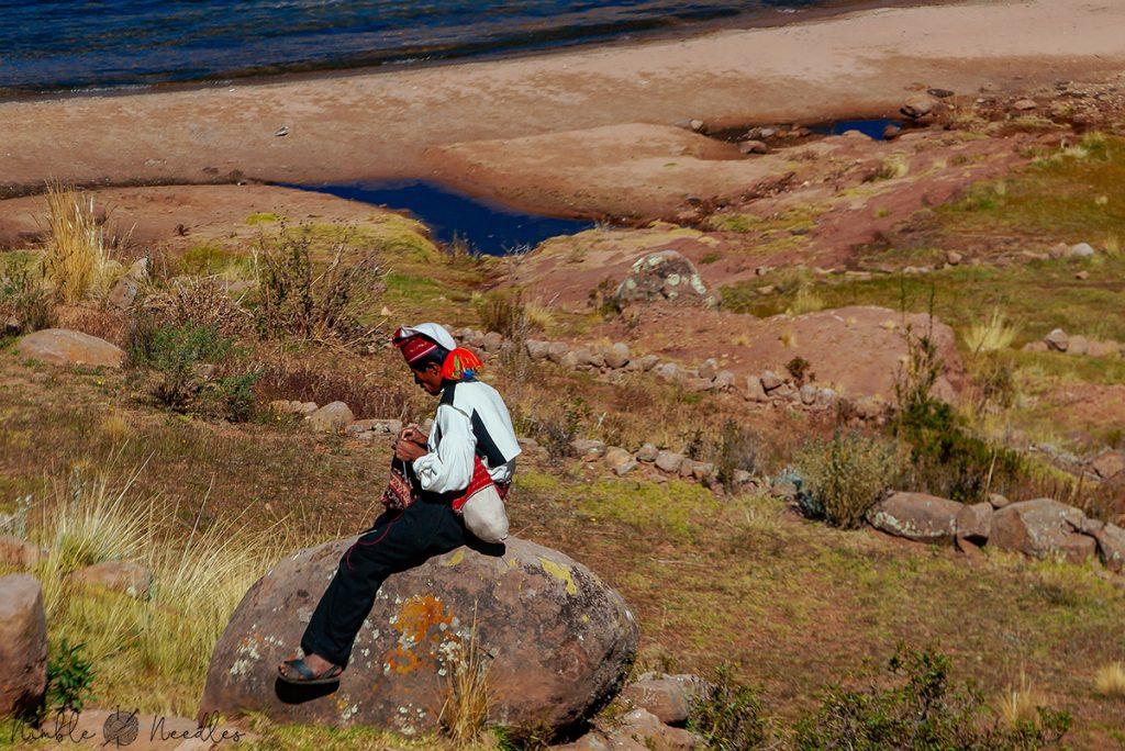 a man near lake titicaca sitting on a rock knitting a hat