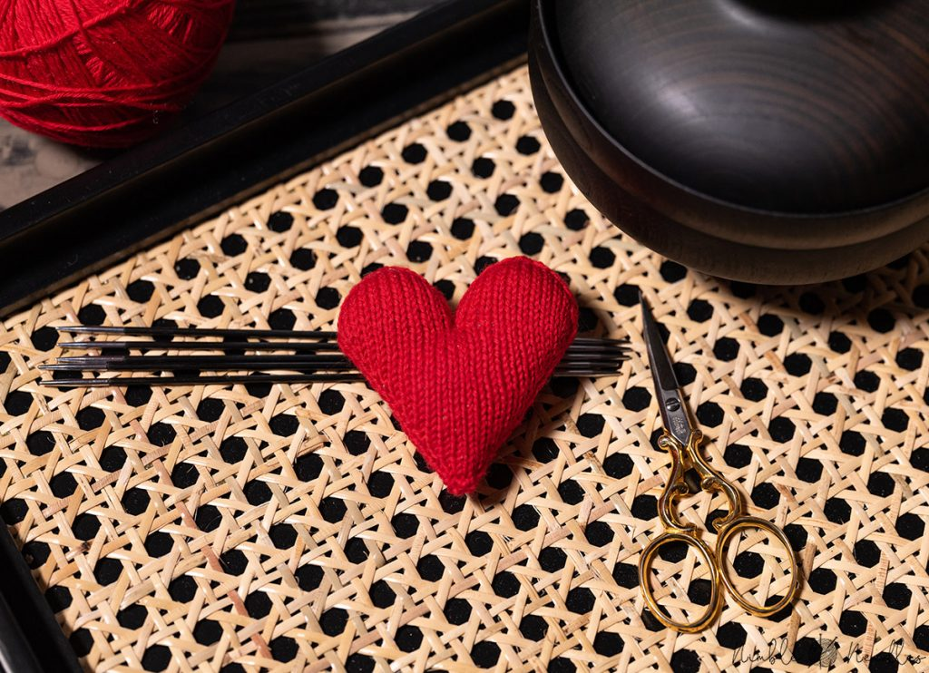 close-up of the knitted heart supported by needles