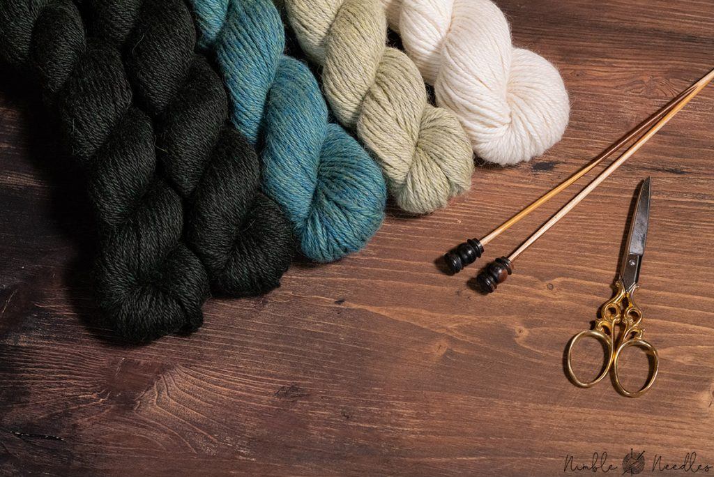 colorful skeins of alpaca knitting yarn on a board with needles