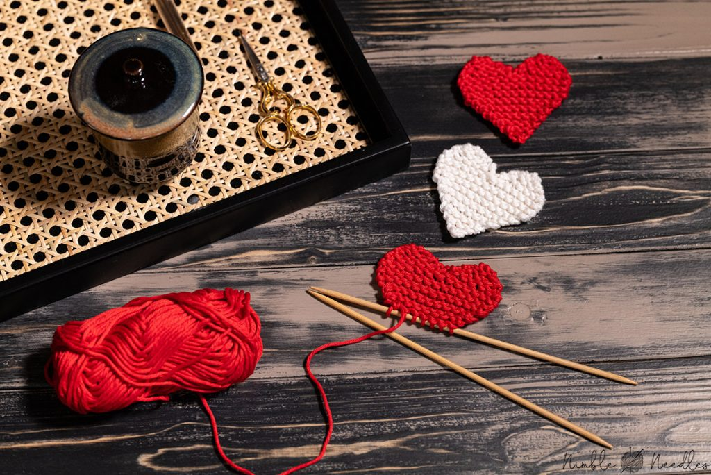 knitting a heart shape with garter stitch with a couple of finished hearts in the background