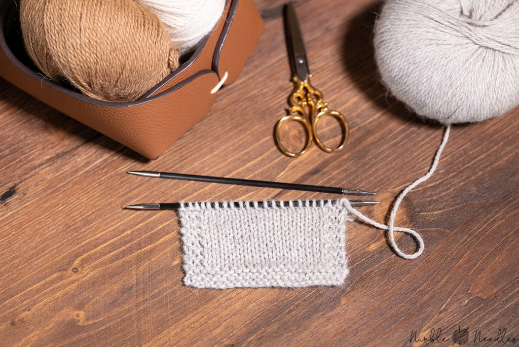 knitting with alpaca yarn on a table with different skeins and tools