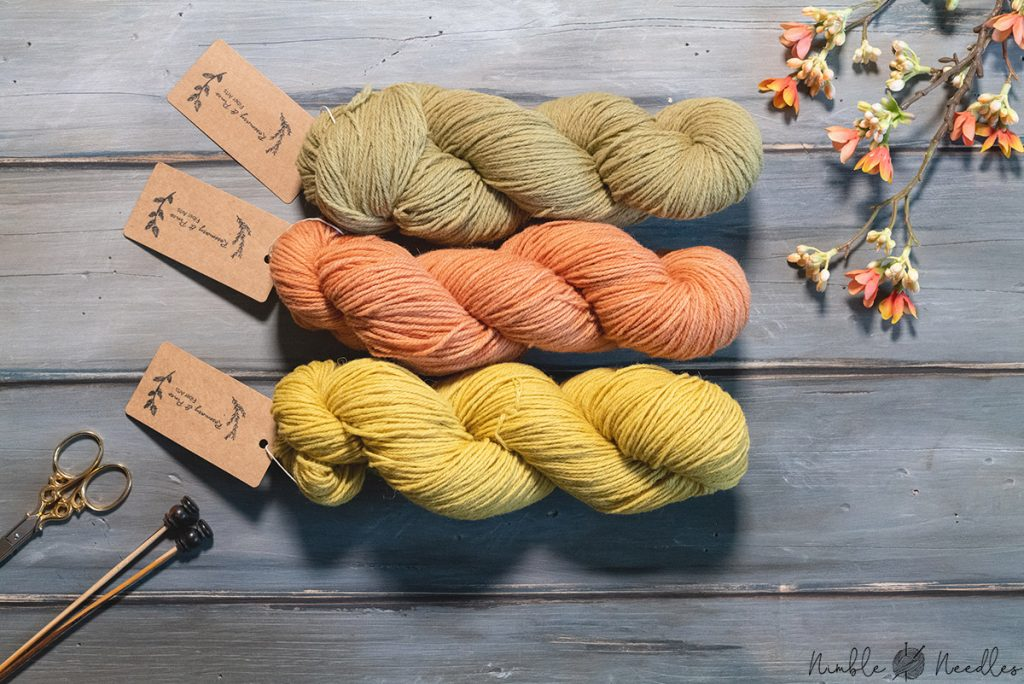 three skeins of naturally dyed plastic free sock yarn in spring colors on a wooden board