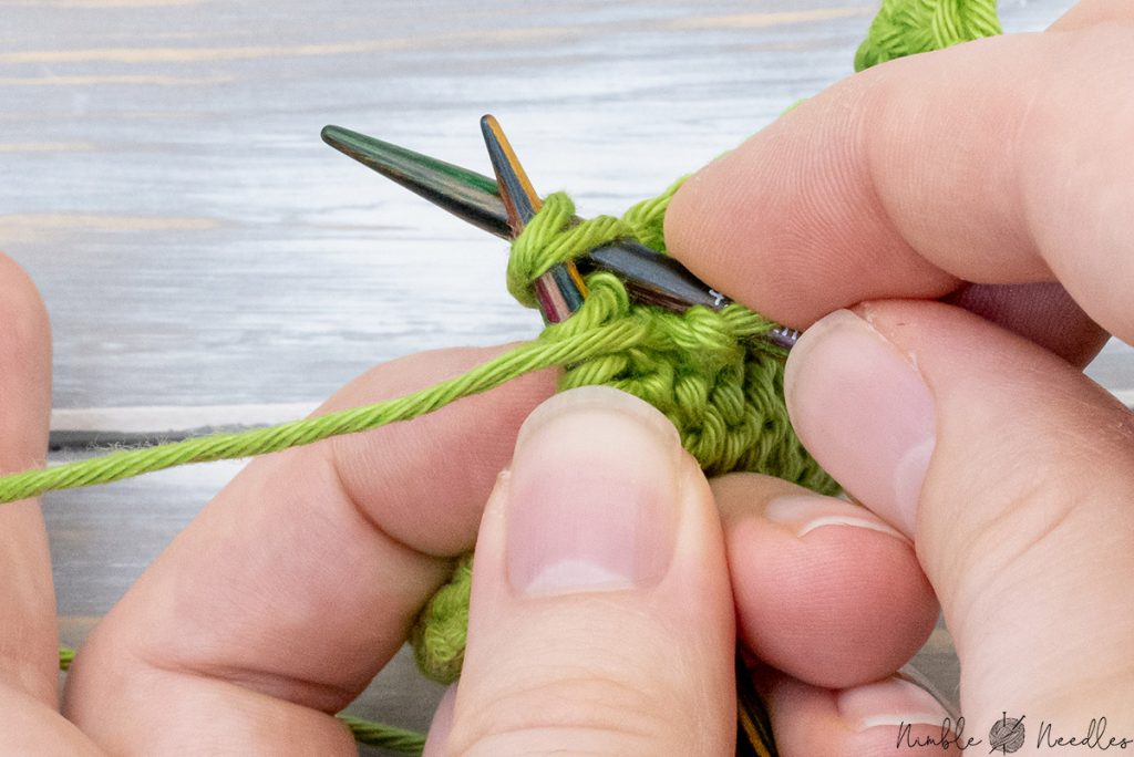 a hand illustrating how to purl three together centered (p3tog)