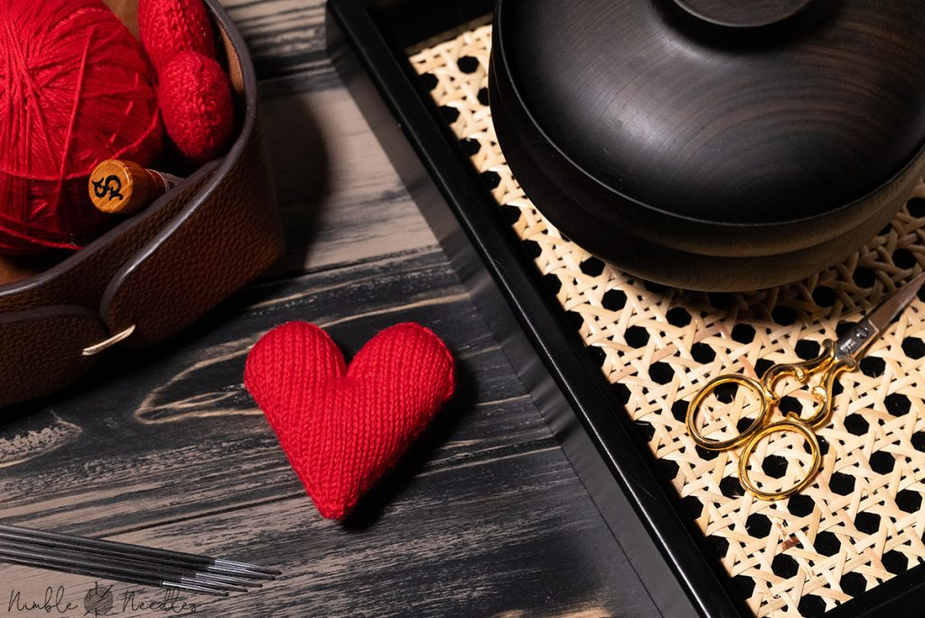 the perfect red heart knitting pattern on a black tray with knitting materials in the background