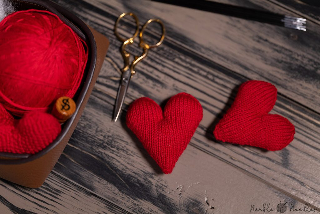 two knitted hearts next to each other on a wooden tray