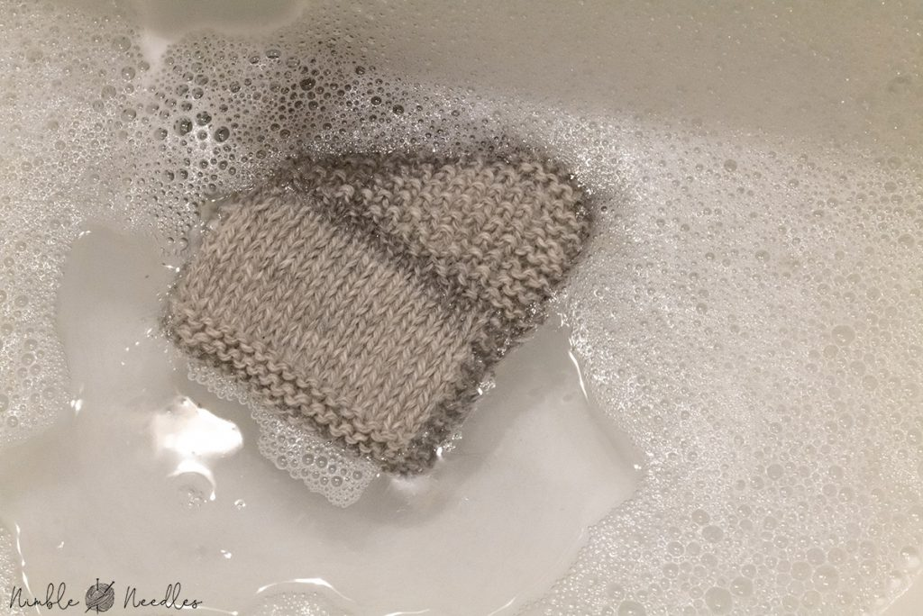 hand washing a swatch of alpaca yarn in warm water and mild soap