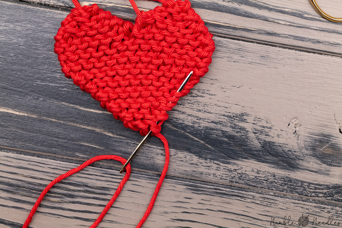 weave in the tails of the heart shape with a tapestry needle through the edge
