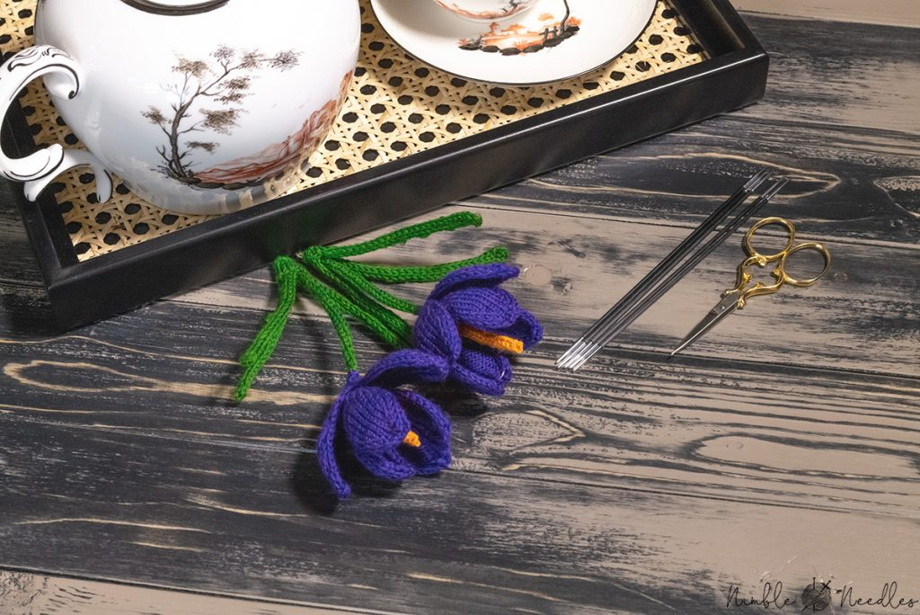 two knitted crocus following a detailed knitting pattern on a wooden board with tea kettle in the background
