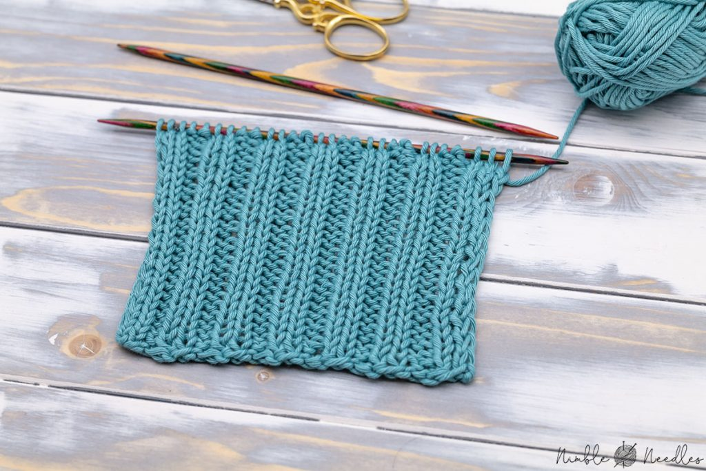 a swatch in the 2x2 rib stitch knitting pattern on a wooden board still on the needles