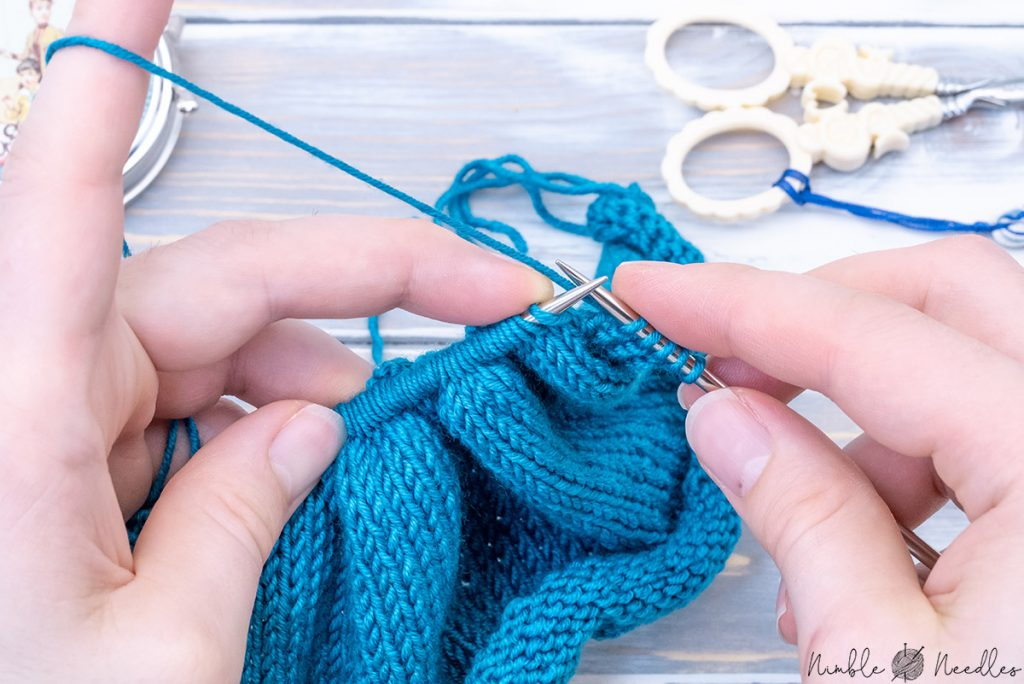 someone bunching up a lot of stitches on the left needle as a preparation for speed knitting