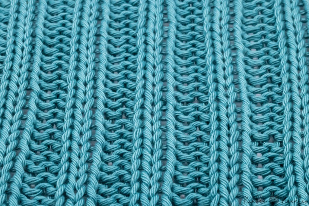 close-up of a 2x2 rib stitch knitting pattern where you can really see the ridges the pattenr is forming
