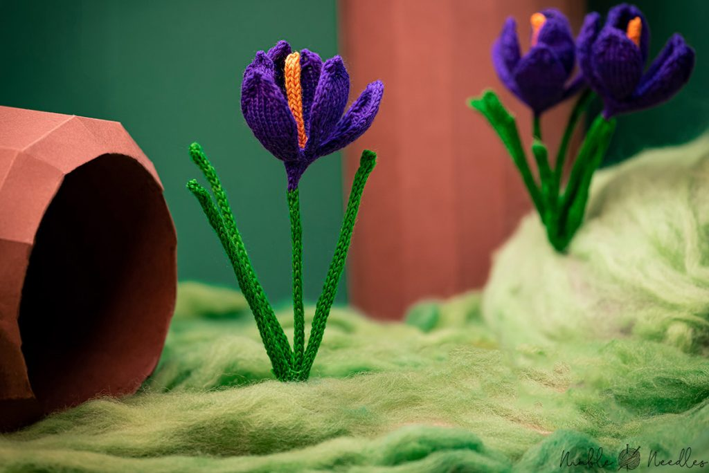 three knitted crocus flowers in a fake wood diorama