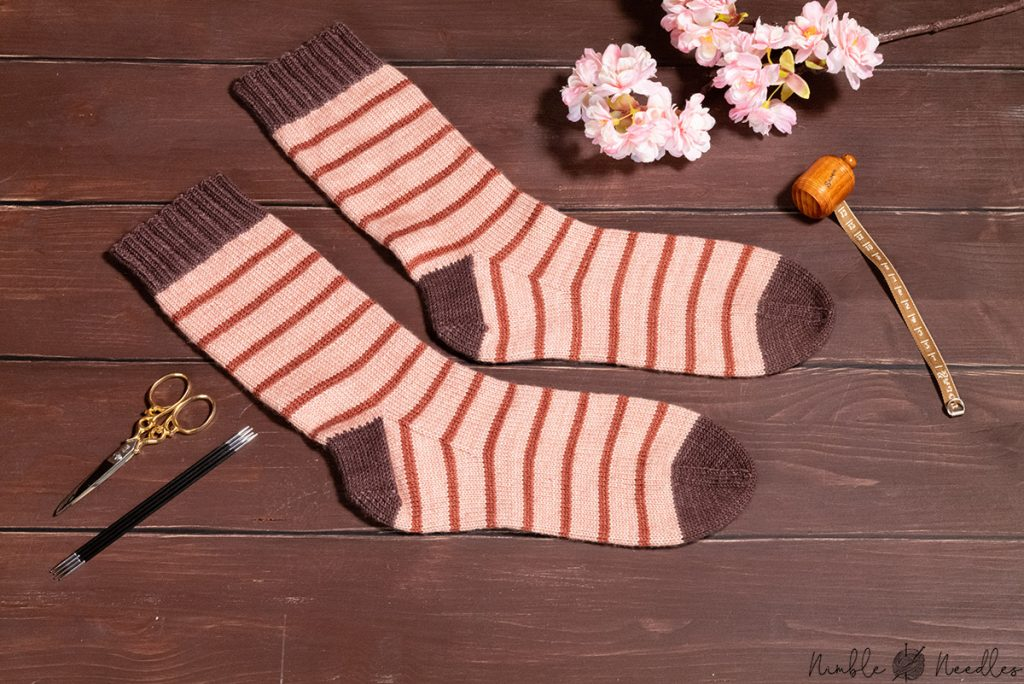 handknit socks following an easy knitting pattern for beginners on a wooden board with flowers in the background
