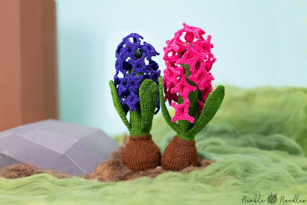the two versions of this hyacinth knitting pattern decorated in a little diorama made of cardboard