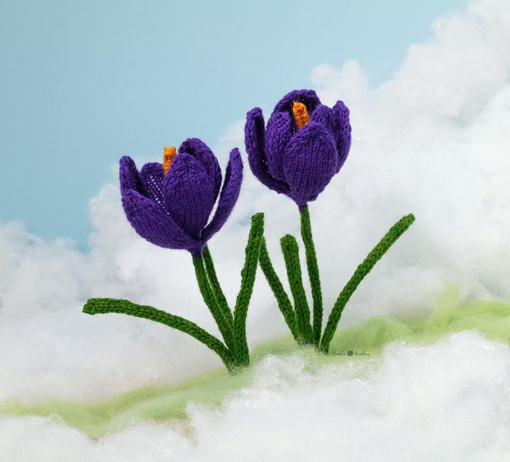 the knitted crocus decorated among fake moss and snow