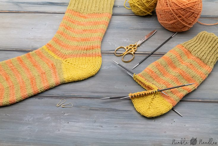 knitting a german short row heel with a finished striped sock in the background