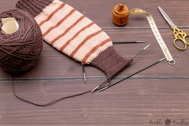 knitting socks with double-pointed needles and various tools in the background