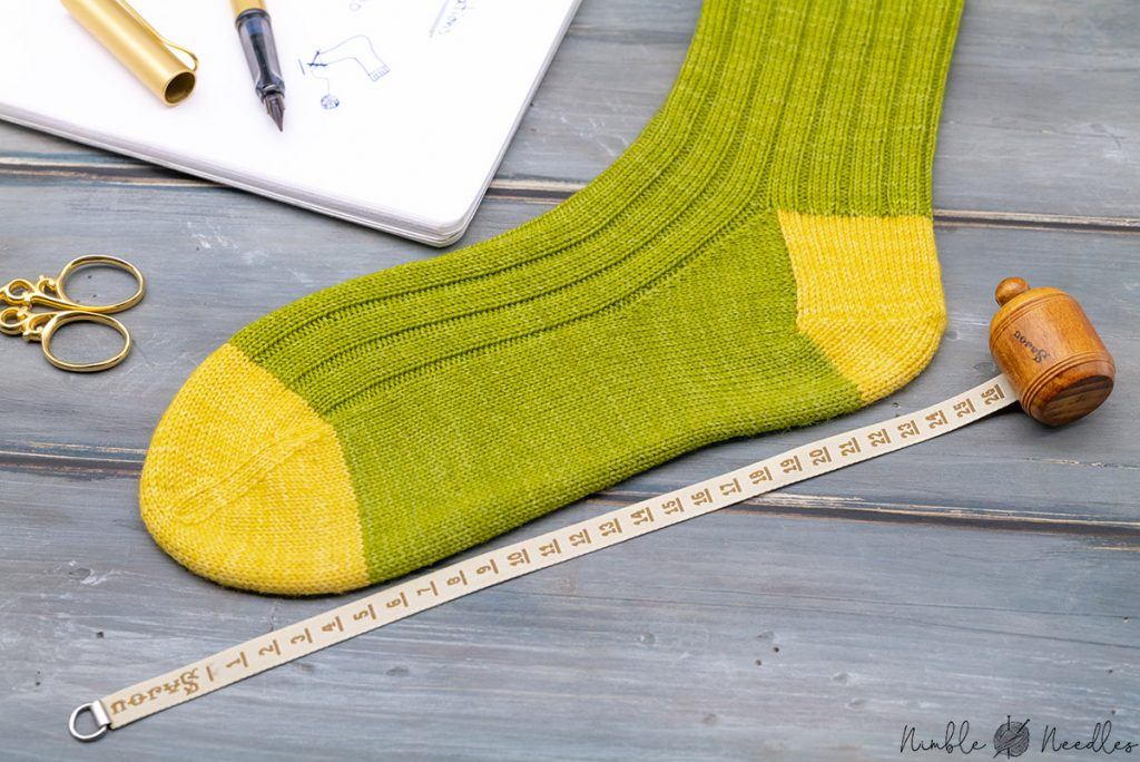 a finished sock with a measuring tape next to it to figure out where you need to start decreasing the toes
