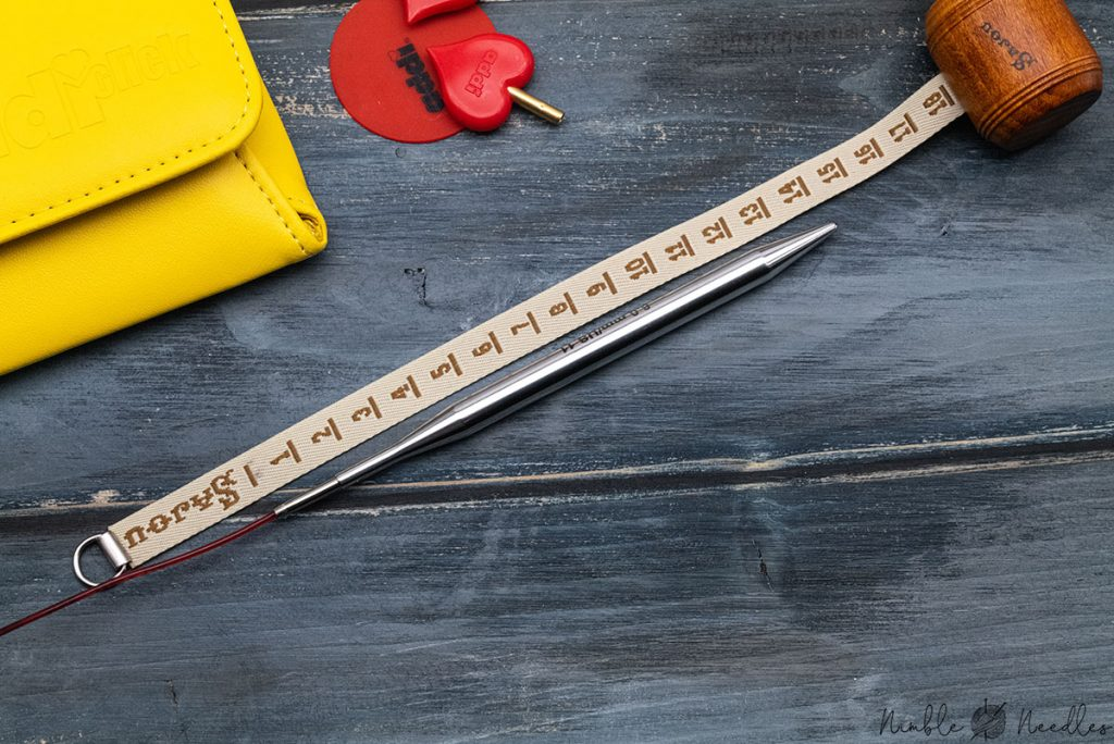 showing the full length of the addi interchangeable knitting needles put together with a measuring tape next to it