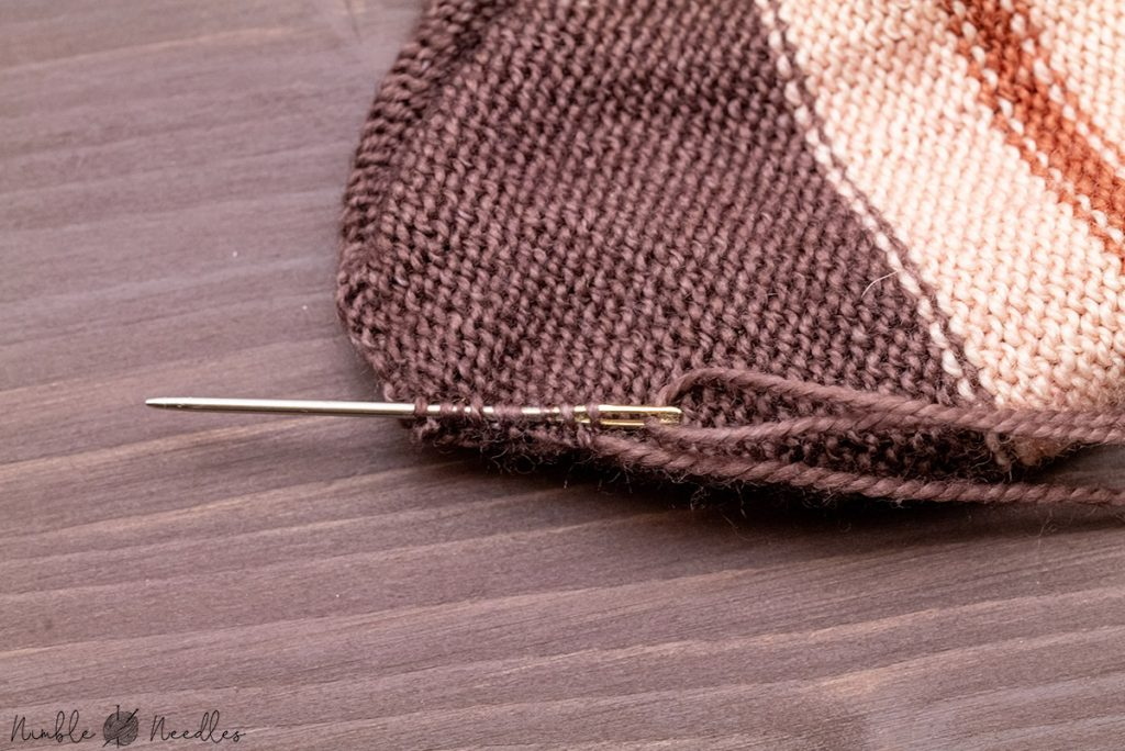 weaving in the tails of the kitchener stitch graft at the toes with a tapestry needle