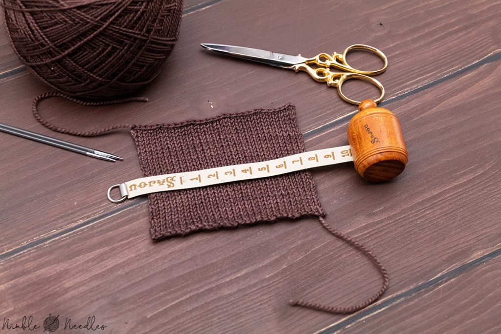measuring the gauge of the swatch for your socks with a measuring tape