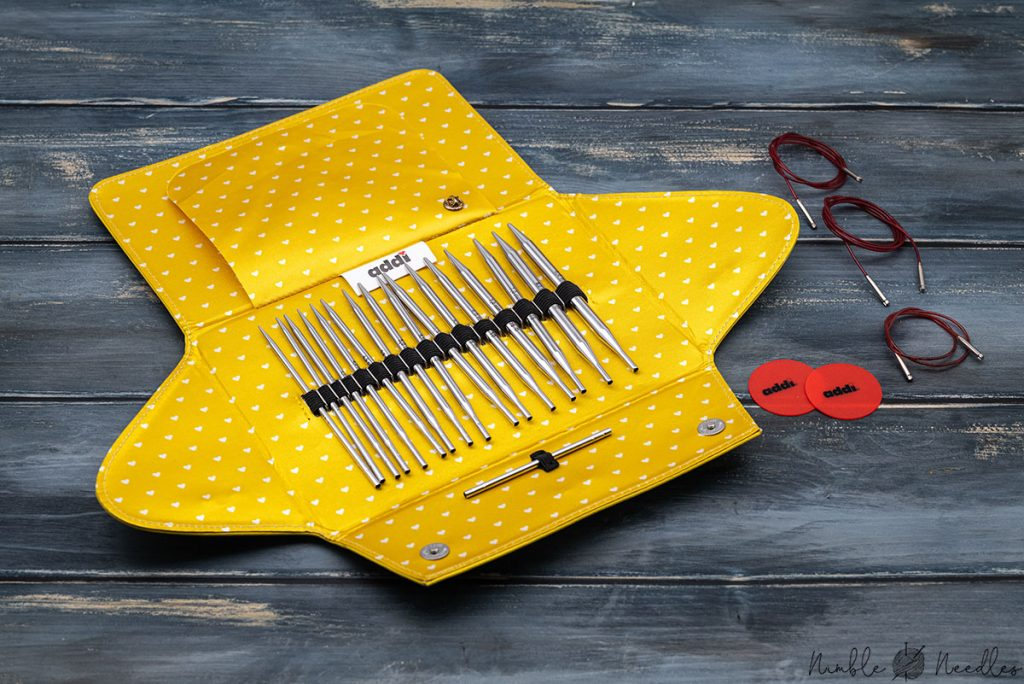 the addi click interchangeable knitting needle set with all contents and accessories next to it