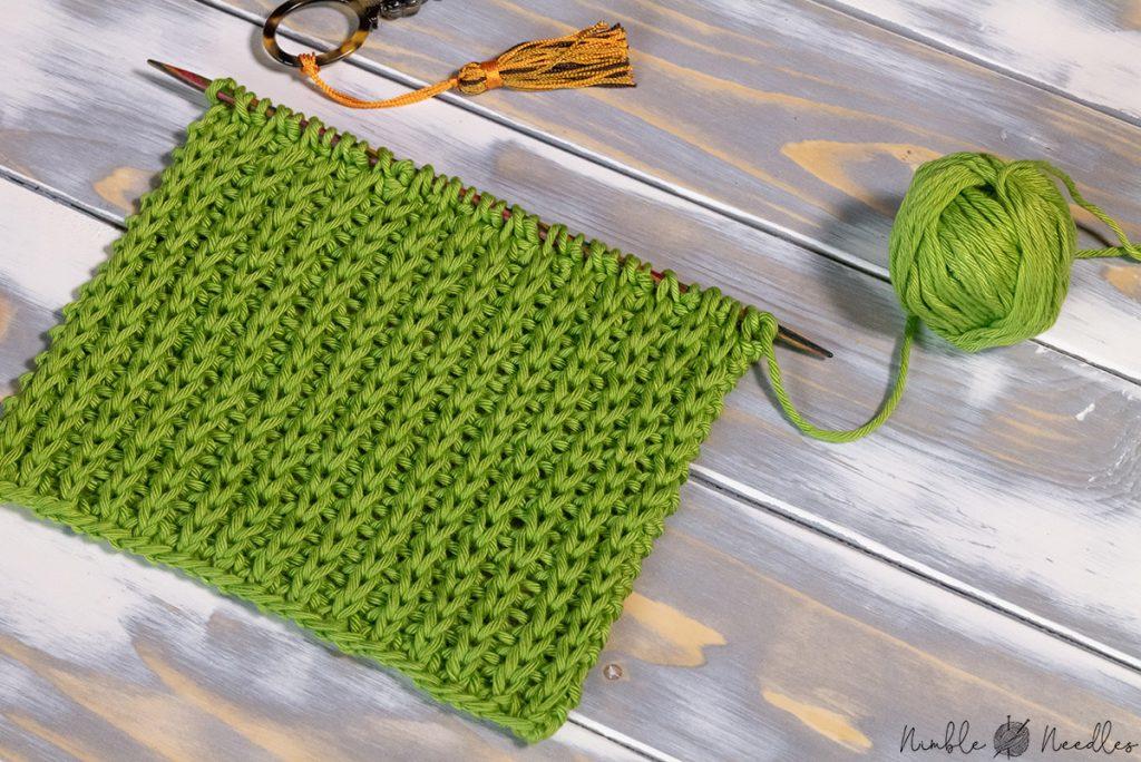 a swatch in the half brioche stitch pattern using green cotton yarn