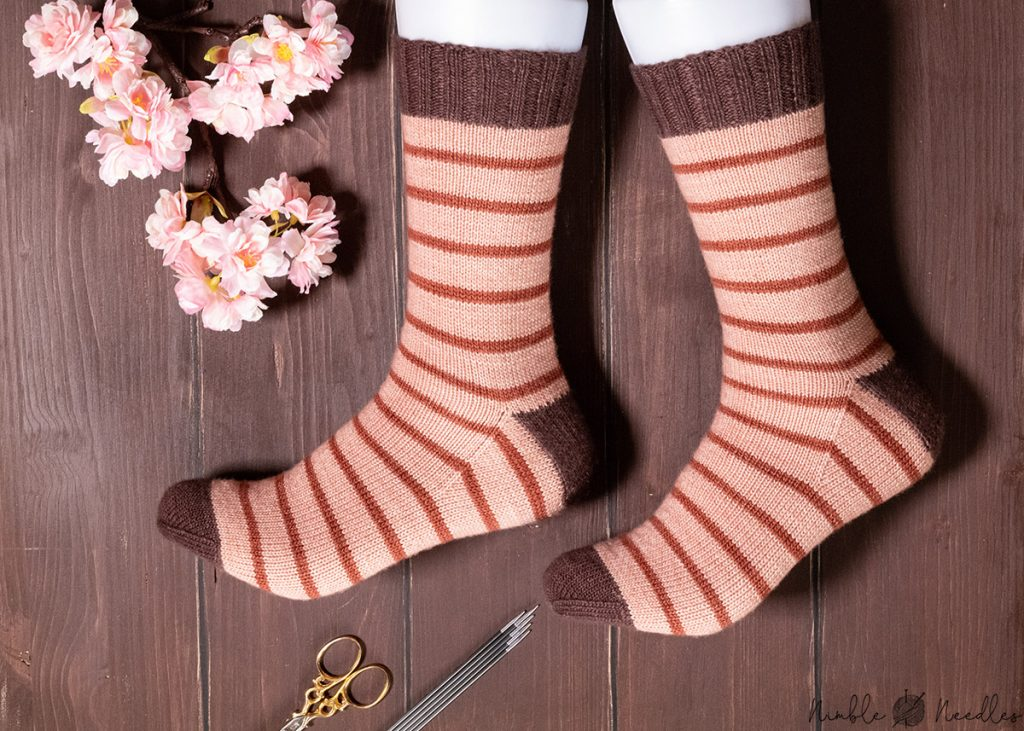 the knitted socks modeled on feet to show how the pattern knits up