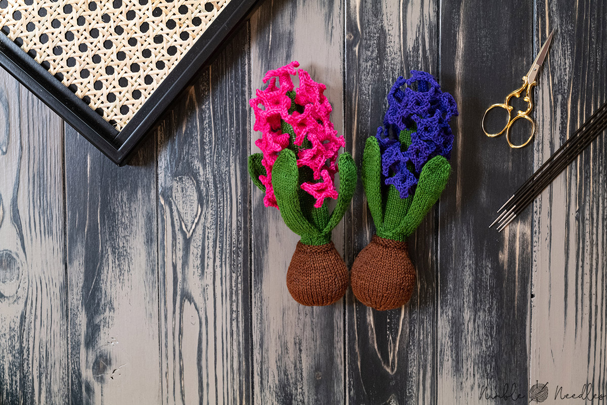 two finished knitted hyacinths on a wooden board with knitting needles and a scissor right next to it