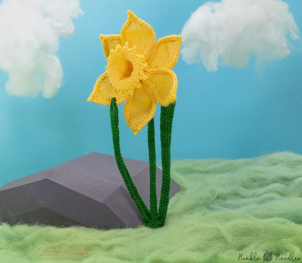 a knitted daffodil sitting in fake moss on fake clouds in the background
