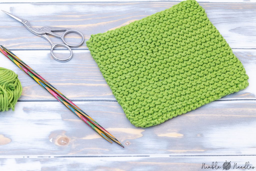a swatch knit in garter stitch knitting pattern with a couple of knitting tools and yarn next to it